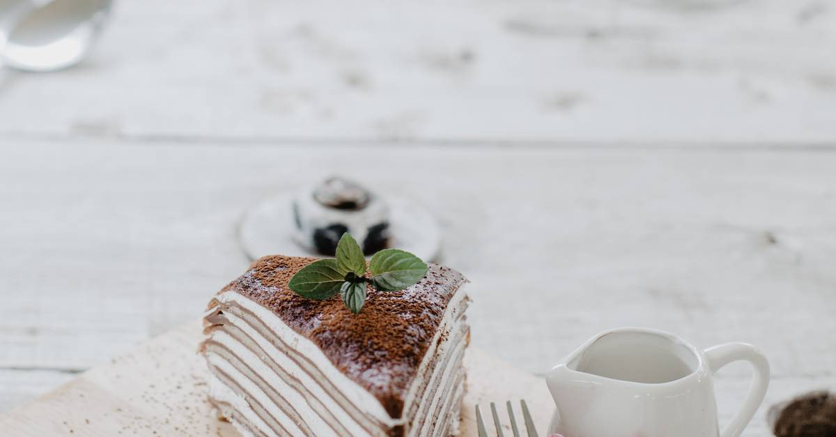 A close up of a piece of cake and a cup of coffee